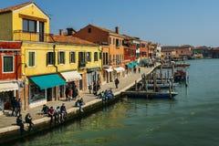 观点的在一条运河旁边的游人有小船的在Murano海岛 库存图片