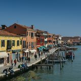 观点的在一条运河旁边的游人有小船的在Murano海岛 图库摄影