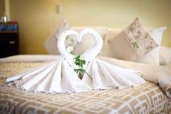 观点的在床单的两只白色毛巾天鹅在旅馆里 免版税库存照片