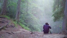 观点的坐在深山沟边缘和采取图片或录影美丽的格子衬衫和长裤的人 影视素材