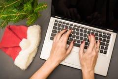 观点的女商人递在膝上型计算机的键入的文本在灰色桌上 顶视图 圣诞节购物、计划和分析 免版税图库摄影