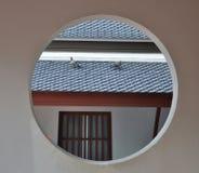观点的屋顶和鸽子通过圆的窗口 免版税库存图片
