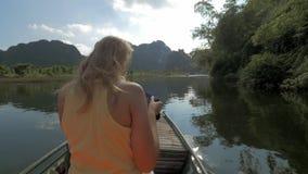 观点的有照相机的白肤金发的妇女在小船 游览在哈隆海湾,小船海岛游览 河内越南 影视素材