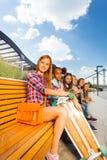 观点的美丽的女孩坐长木凳 免版税图库摄影