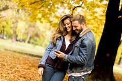观看一个巧妙的电话的愉快的夫妇 库存图片