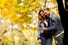 观看一个巧妙的电话的愉快的夫妇 图库摄影
