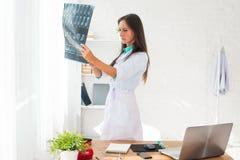 观看一个耐心X-射线的少妇医生  免版税库存图片