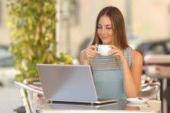 观看一台膝上型计算机的轻松的妇女在餐馆 库存图片
