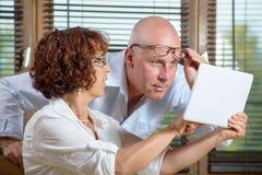 观看一种数字式片剂的一对资深夫妇在办公室 免版税库存照片