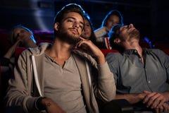 观看一部乏味影片的青年人在戏院 免版税库存照片