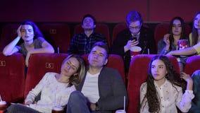 观看一部乏味电影在戏院,爱的夫妇睡觉的年轻人 股票视频