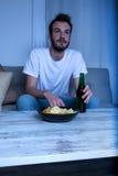 观看一部哀伤的电影的年轻人在与芯片和啤酒的晚上 免版税库存照片