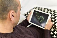 观看一部电影或一个系列在他的片剂的年轻人 库存照片
