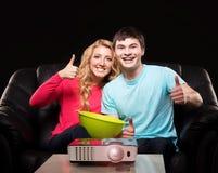 观看一部电影或体育广播在激光放映机的年轻家庭 库存图片