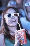 观看一部3D电影的少妇在剧院 免版税库存图片