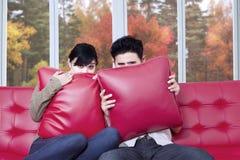 观看万圣夜电影的害怕的夫妇 免版税库存图片
