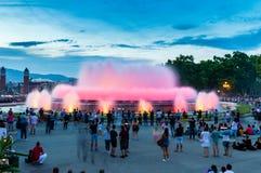 观看不可思议的喷泉光的未定义人民在晚上显示 免版税库存照片