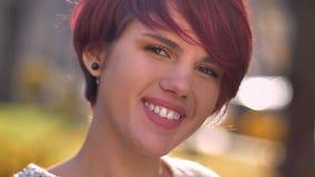 观看与挥动的微笑的年轻凉快的白种人粉发的女孩特写镜头画象入在晴朗的公园的照相机 免版税库存图片