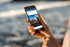 观看与新的iPhone的妇女Instagram新闻 库存照片