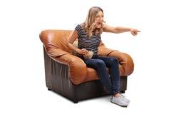 观看事的笑的妇女热闹在电视 免版税图库摄影