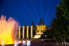 观看五颜六色的喷泉的游人 库存图片