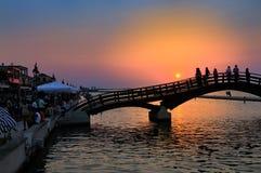 观看五颜六色的日落桥梁的人剪影 库存图片