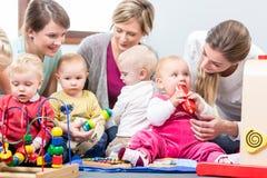 观看他们的婴孩的三个愉快的母亲使用与安全玩具 免版税库存照片