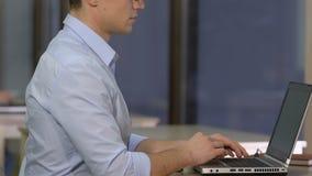 观看他的姿势的年轻男性雇员,当研究计算机,脊椎关心时 影视素材