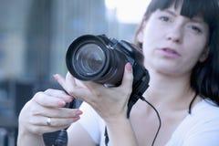 观看他的照片的年轻女性摄影师在背面 免版税库存图片