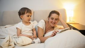 观看作为他的母亲的可爱的小孩男孩使用数字式片剂在床 免版税库存照片