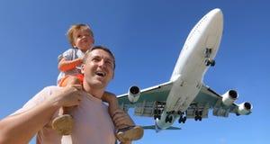 观看使飞机降落的父亲和儿子 库存图片