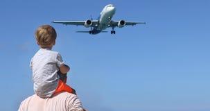 观看使飞机降落的父亲和儿子 免版税图库摄影