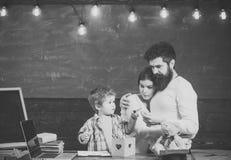 观看儿子成功的骄傲的父母 繁忙的面孔图画或文字的男孩 父母支持概念 父母观看他们 免版税库存图片