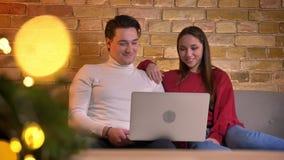 观看入膝上型计算机和笑在家庭环境的沙发的快乐的白种人朋友特写镜头画象  股票录像