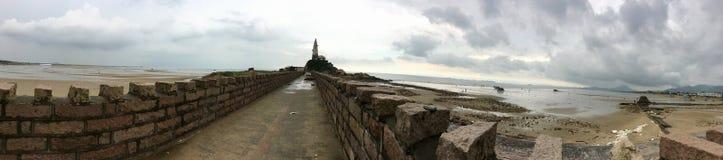观看全景老石墙到灯塔在海在中国 早晨海风景在一个多云雨天 免版税库存照片