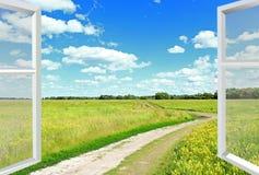 观看到云彩草甸和从窗口的乡下公路 免版税库存照片