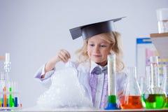 观看化学反应的微笑的逗人喜爱的化学家 库存图片