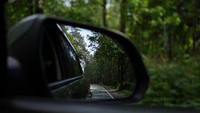 观看后视镜当在乡下公路的汽车驱动 4K 股票录像