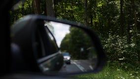 观看后视镜当在乡下公路的汽车驱动 4K 影视素材