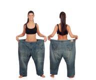 观看向前和在稀薄的女孩后用大裤子 免版税库存照片