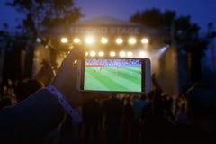 观看在一个智能手机的屏幕上的一场足球比赛在音乐会的,音乐节 免版税库存图片