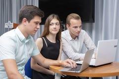 观看在一台膝上型计算机的小组两名年轻欣快学生考试结果在桌里 免版税库存照片