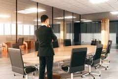 观看在与椅子的圆的会议桌上的商人在Th 图库摄影