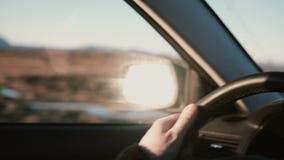 观看在乡下沙漠路inbeautiful日落的汽车里面 男性手特写镜头视图在轮子的 影视素材