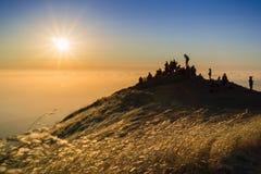 观看在云彩海的人们五颜六色的日落  免版税图库摄影