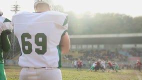 观看在体育场的替补球员活跃橄榄球赛,概略的并列争球 股票录像