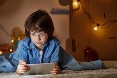 观看在剪贴板的感兴趣的男孩一部动画片 库存图片