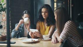 观看在咖啡馆的小组年轻女人智能手机屏幕笑的饮用的咖啡 股票录像