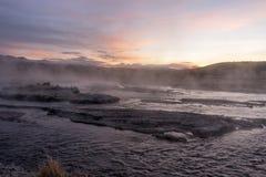 观看在地热水一条通入蒸汽的河的跳动道路日出  免版税库存图片