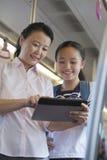 观看在地铁的微笑的母亲和女儿一部电影在一种数字式片剂 库存照片